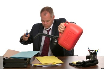Businessman about to set fire to a pile of documents